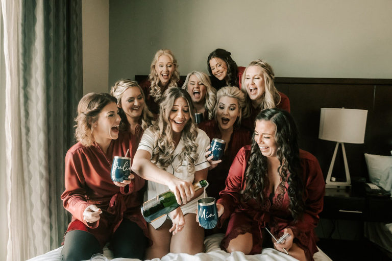 Tampa Bay Bridesmaids and Bride Popping Champagne Before She Changes Her Last Name Bridal Party Getting Ready Inspiration, Wearing Matching Burgundy Silk Robes with Custom Navy Stemless Wine Tumblers
