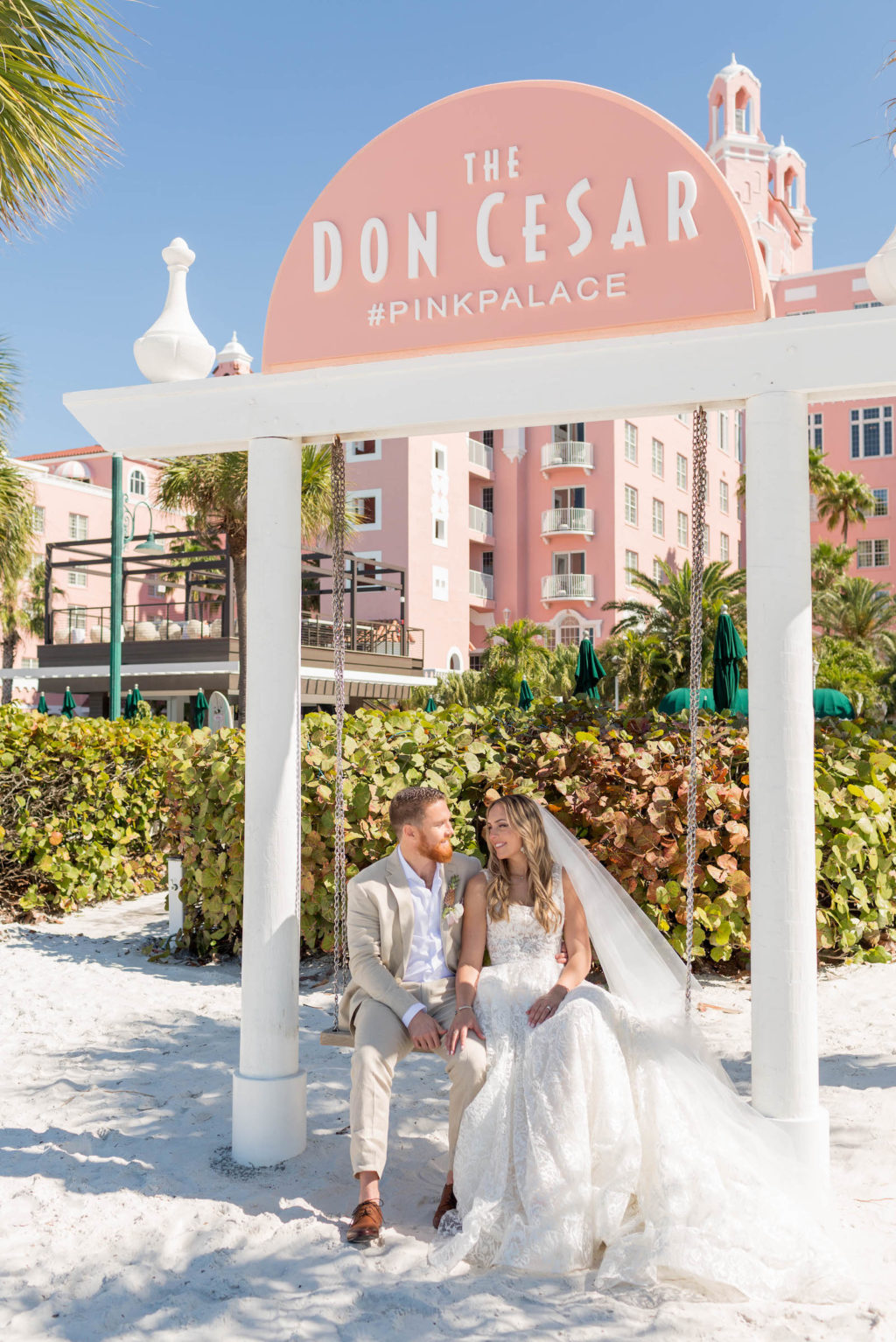 Bride and Groom Outdoor Portrait on Beach Swing at St. Pete Beach Wedding Venue The Don CeSar Pink Palace | Monique Lhuillier Designer Wedding Dress A Line Ballgown Lace Bridal Gown | Groom Wearing Casual Khaki Suite
