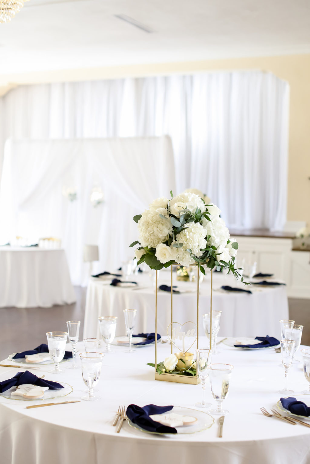 Classic Wedding Reception Decor, White Table Linens, Navy Blue Linen Napkins, Gold Flatware and Stand with White Hydrangeas, Roses and Greenery Floral Centerpiece | Tampa Bay Wedding Photographer Lifelong Photography Studio | Wedding Planner Core Concepts | Wedding Rentals A Chair Affair | Kate Ryan Event Rentals