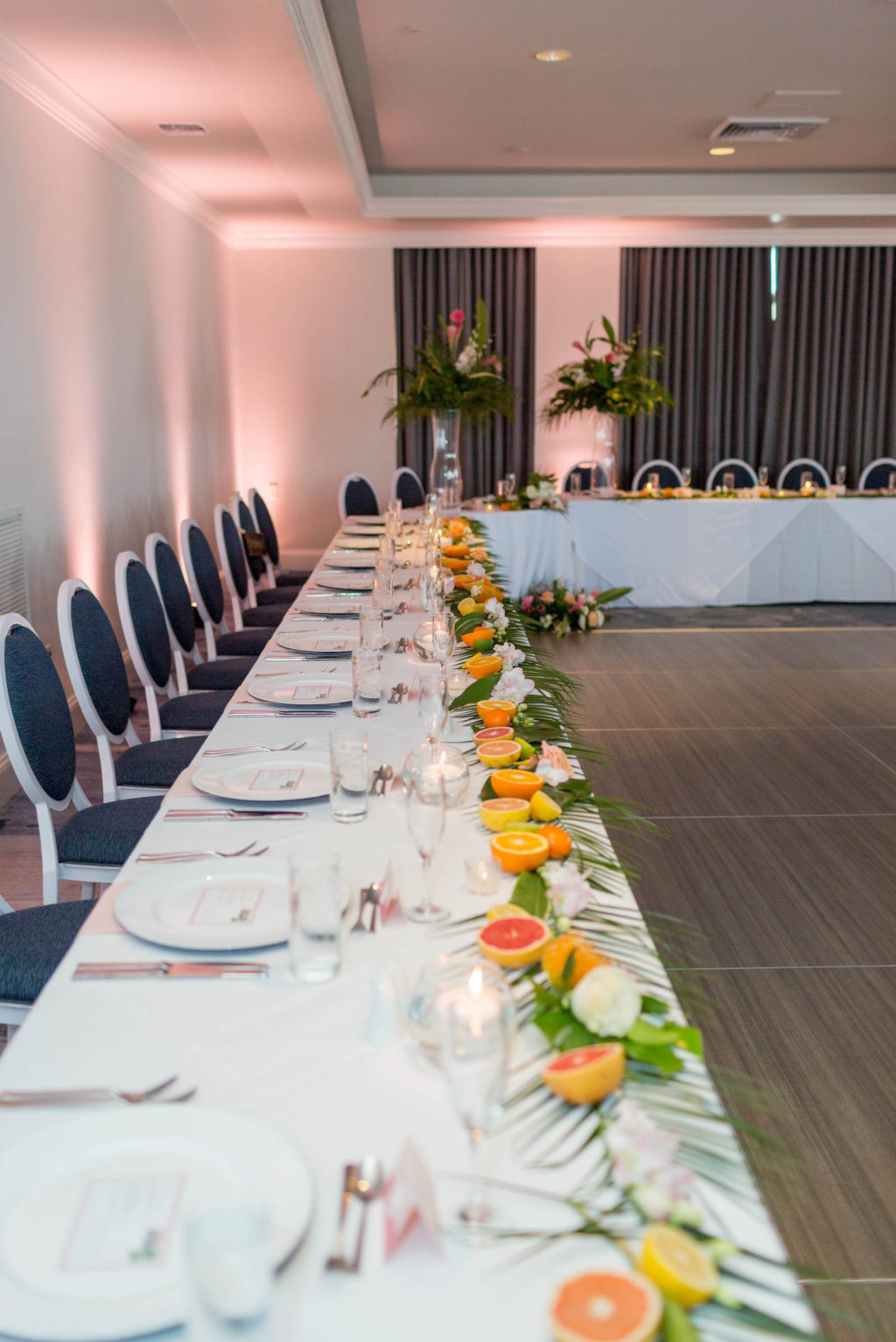 Wedding Head Table | Long Feasting Table with Palm Frond Leaves and Cut Citrus Oranges Lemons and Grapefruit Garland Runner