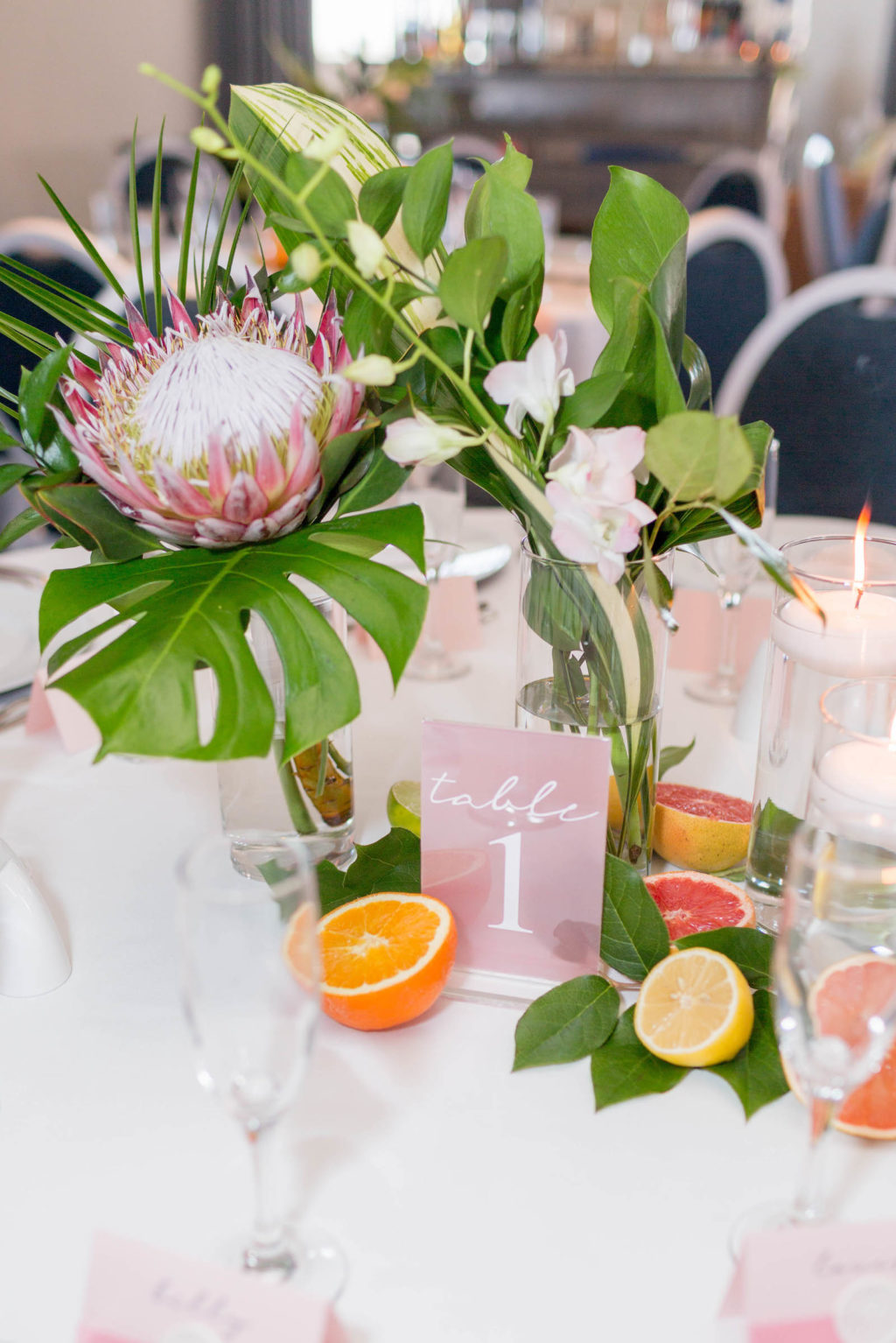 Tropical Florida Citrus Wedding Centerpieces with Cut Oranges Lemons and Grapefruit and Vases of Monstera Palm Greenery and Pink Orchids and Protea with Floating Candles | Pink Acrylic Wedding Table Number