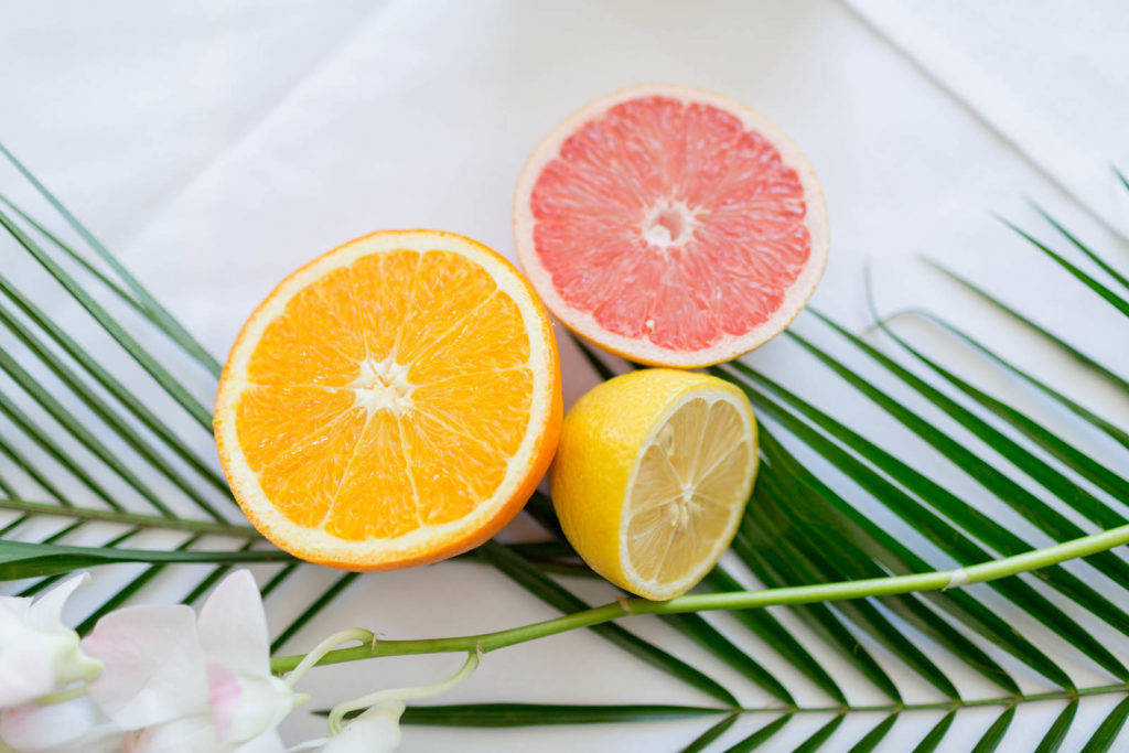 Tropical Florida Citrus Wedding Centerpieces with Cut Oranges Lemons and Grapefruit and Palm Frond Leaves