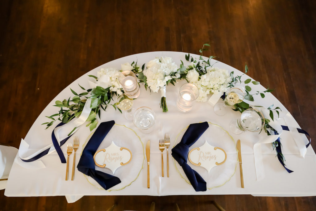 Classic Wedding Reception Decor, Half Moon Sweetheart Table with White Table Linen, Navy Blue Linen Napkins, Gold Flatware, Gold Rimmed and Milky White Scalloped Chargers, Hydrangeas, Roses and Greenery Floral Arrangements | Tampa Bay Wedding Photographer Lifelong Photography Studio | Wedding Planner Core Concepts | Wedding Rentals A Chair Affair | Kate Ryan Event Rentals