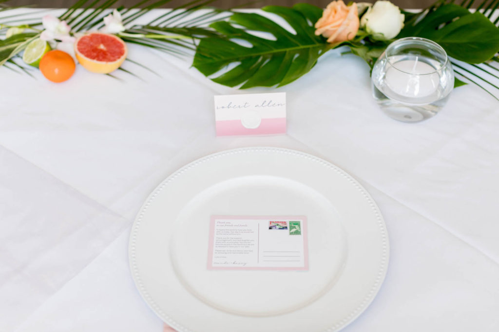 Tropical Florida Citrus Wedding Centerpieces with Cut Oranges Lemons and Grapefruit and Monstera Palm Greenery Garland Runner | Wedding Reception Place Setting with Pink Napkin, Pink Place Card, and Postcard Favor