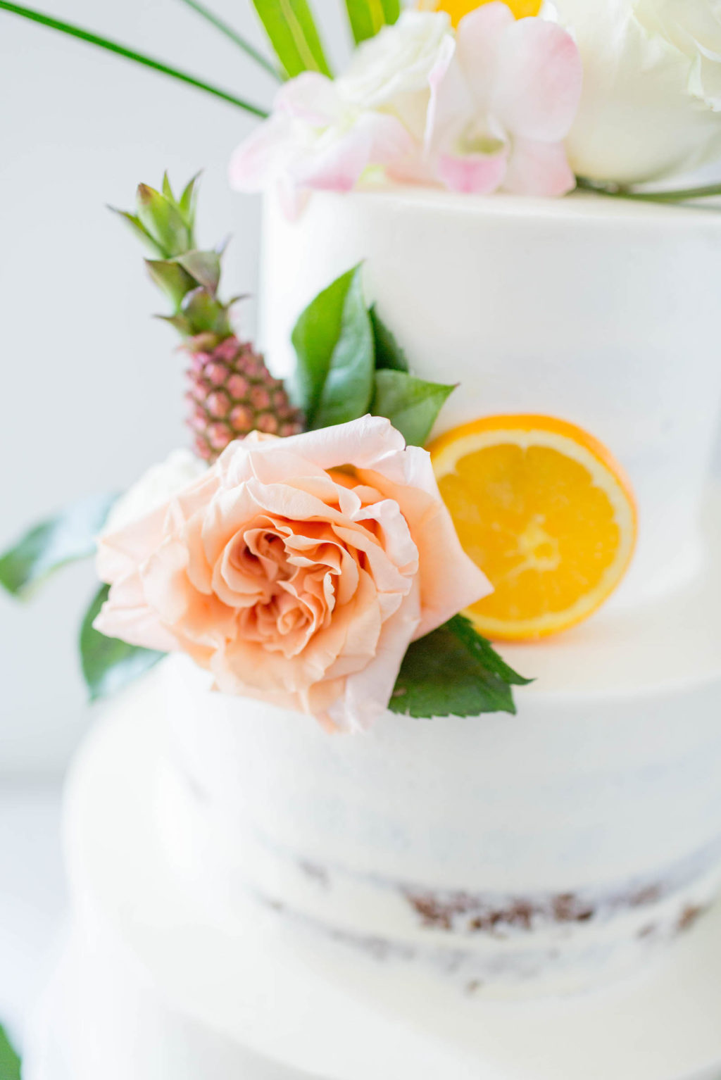 Tropical Beach Wedding Cake | Three Tier Semi Naked Half Iced Buttercream Wedding Cake with Tropical Greenery Monstera Leaf, Orange Slices and Mini Ornamental Pineapple, Blush Pink Roses and Protea by The Artistic Whisk