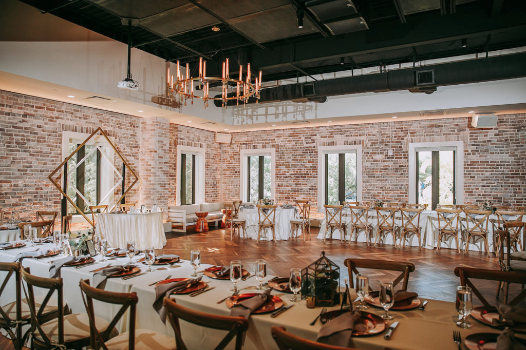 Indoor Historic Venue Brick Wall Wedding Reception at Downtown St. Pete Wedding Venue Red Mesa Events | Cross Back Wood French Country Chairs with White Table Linens on Long Feasting Tables | Perfecting the Plan
