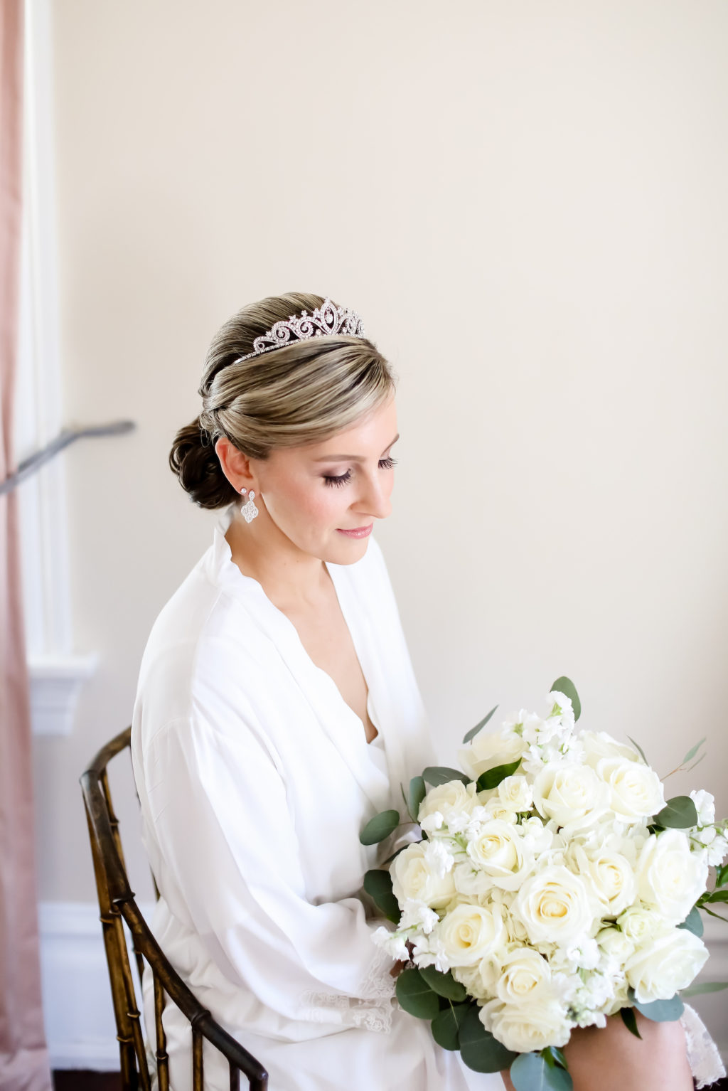 Classic Bride with Hair in Bun and Rhinestone Headband Getting Wedding Ready in White Robe Holding White Roses Floral Bouquet | Tampa Bay Wedding Photographer Lifelong Photography Studio
