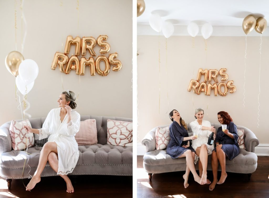 Florida Bride Getting Wedding Ready in White Robe Sitting on Couch Holding Gold and White Latex Balloons, Letter Foil Balloons Backdrop with New Last Name, Bridesmaids in Blue Robes Popping Bottle of Champagne | Tampa Bay Wedding Photographer Lifelong Photography Studio