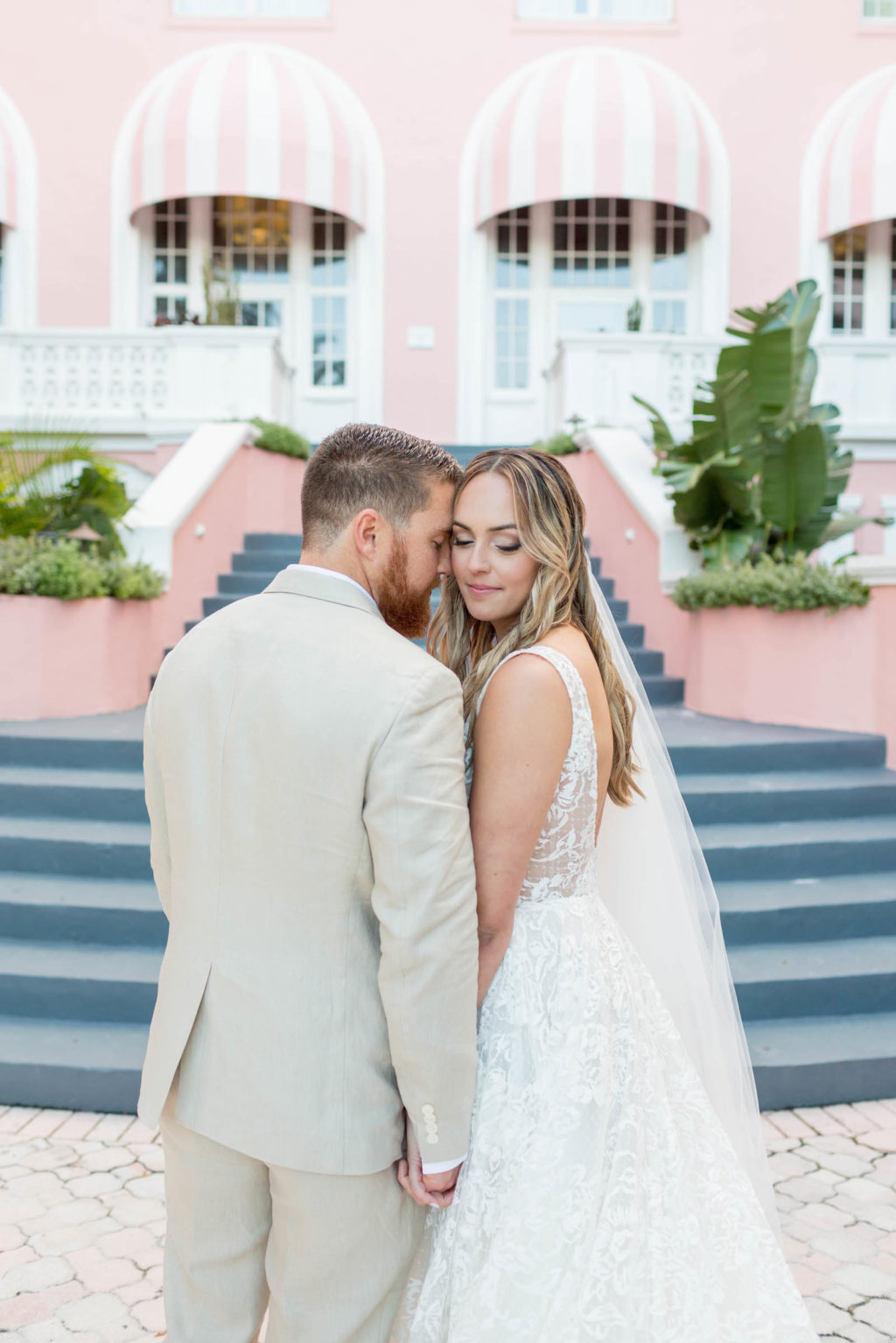 Bride and Groom Outdoor Portrait Staircase at St. Pete Beach Wedding Venue The Don CeSar Pink Palace | Monique Lhuillier Designer Wedding Dress A Line Ballgown Lace Bridal Gown | Groom Wearing Casual Khaki Suite