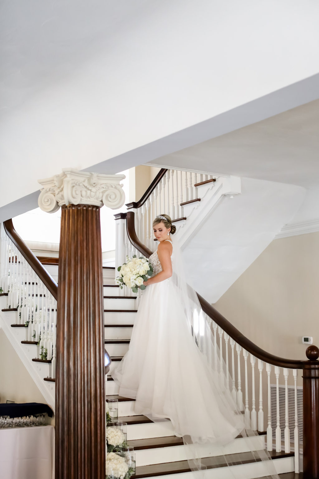 Classic Bride in Tulle Skirt A-Line Wedding Dress Holding White Floral Bouquet on Staircase of Wedding Venue The Orlo | Tampa Bay Wedding Photographer Lifelong Photography Studio