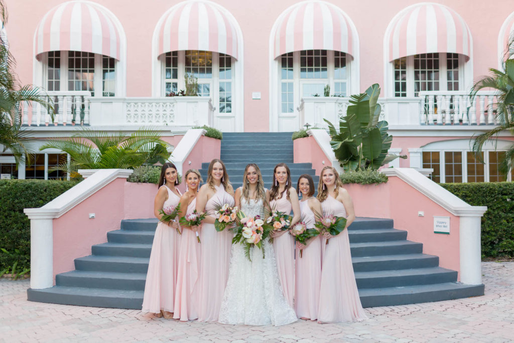 Bride and Bridesmaid Outdoor Portrait Staircase at St. Pete Beach Wedding Venue The Don CeSar Pink Palace | Monique Lhuillier Designer Wedding Dress A Line Ballgown Lace Bridal Gown | Soft Light Blush Pink Long Chiffon Bridesmaids Dresses by David's Bridal | Tropical Wedding Bride and Bridesmaid Bouquets with Monstera Leaf Greenery and Pink Protea