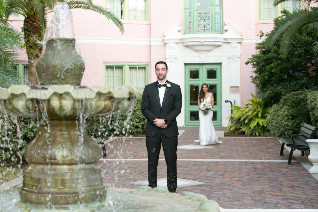 First Look Photo with Groom in Classic Black Tux, Bride Walking Behind in Courtyard of Hotel St. Pete Wedding Venue The Vinoy Renaissance | Tampa Bay Wedding Photographer Carrie Wildes Photography