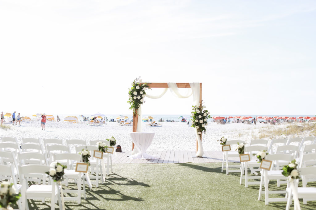 Timeless Wedding Ceremony Decor, Waterfront Lawn, Wooden Arch with White Linen Drapery, White Roses and Greenery Floral Arrangements | Tampa Bay Wedding Photographer Lifelong Photography Studio | Clearwater Beach Wedding Venue Sandpearl Resort | Wedding Florist Iza's Flowers | Wedding Planner Blue Skies Weddings and Events