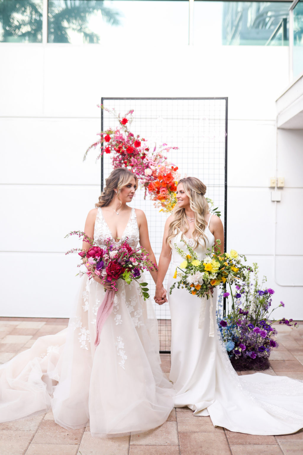 Gay LGBTQ+ Pride Wedding, Lesbian Brides Holding Hands with Red and Yellow Floral Bouquets, Black Metal Grid Mesh Rectangle Arch with Rainbow Flower Arrangement, Pink, Orange, Purple and Blue   Tampa Bay Wedding Planner Stephany Perry Events   Rooftop Wedding Venue Hotel Alba Tampa