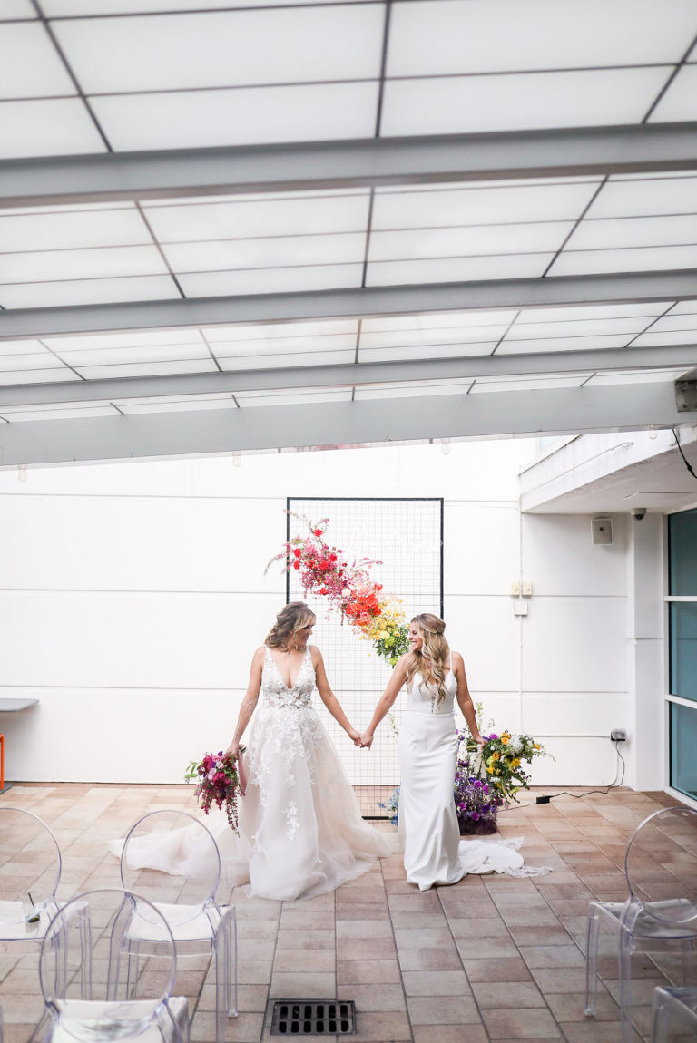 Gay LGBTQ+ Pride Wedding, Lesbian Brides Holding Hands with Red and Yellow Floral Bouquets, Black Metal Grid Mesh Rectangle Arch with Rainbow Flower Arrangement, Pink, Orange, Purple and Blue | Tampa Bay Wedding Planner Stephany Perry Events | Rooftop Wedding Venue Hotel Alba Tampa