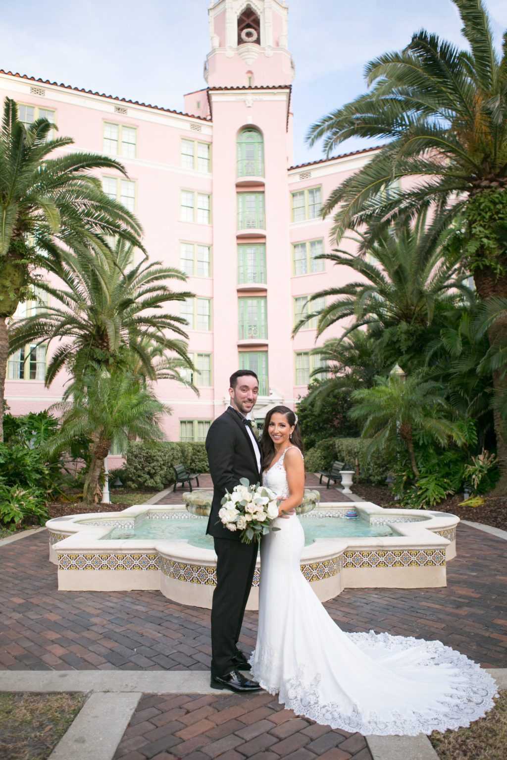 Elegant Classic Bride in Romantic Lace Train and Crepe Fitted Wedding Dress Holding White and Greenery Floral Bouquet, Groom in Classic Black Tux in Courtyard of St. Pete Wedding Venue The Vinoy Renaissance | Tampa Bay Wedding Photographer Carrie Wildes Photography | Wedding Dress Shop Isabel O'Neil Bridal Collection