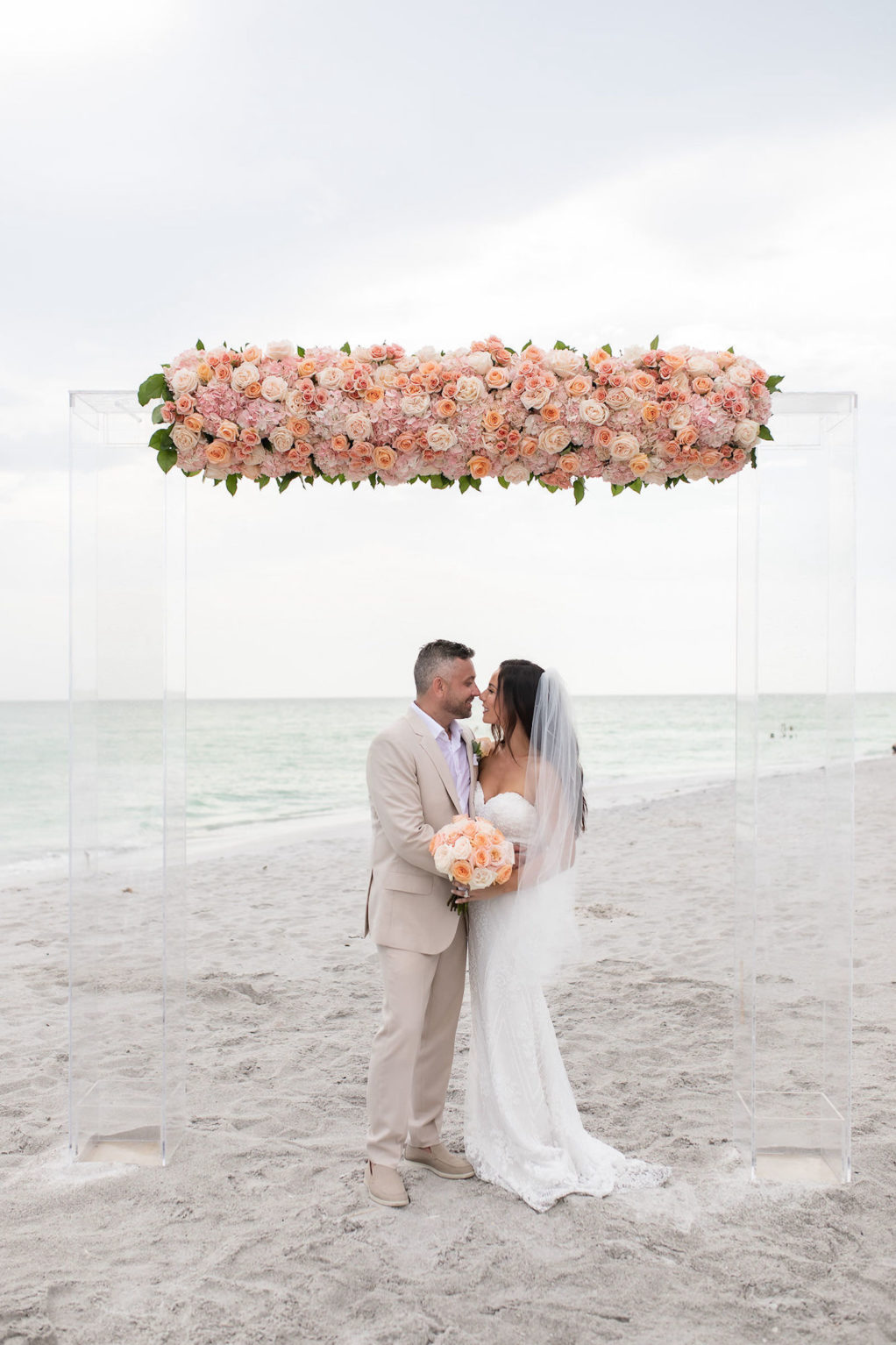 Outdoor Bride and Groom Portrait at Florida Beach Wedding at Sarasota Wedding Venue The Resort at Longboat Key Club | Ceremony Backdrop with Clear Acrylic Arch and Floral Arrangement of Peach Pink and Coral Roses | Bride Wearing Strapless Sheath Wedding Gown by Tara Keilly | Groom Wearing Casual Khaki Suit