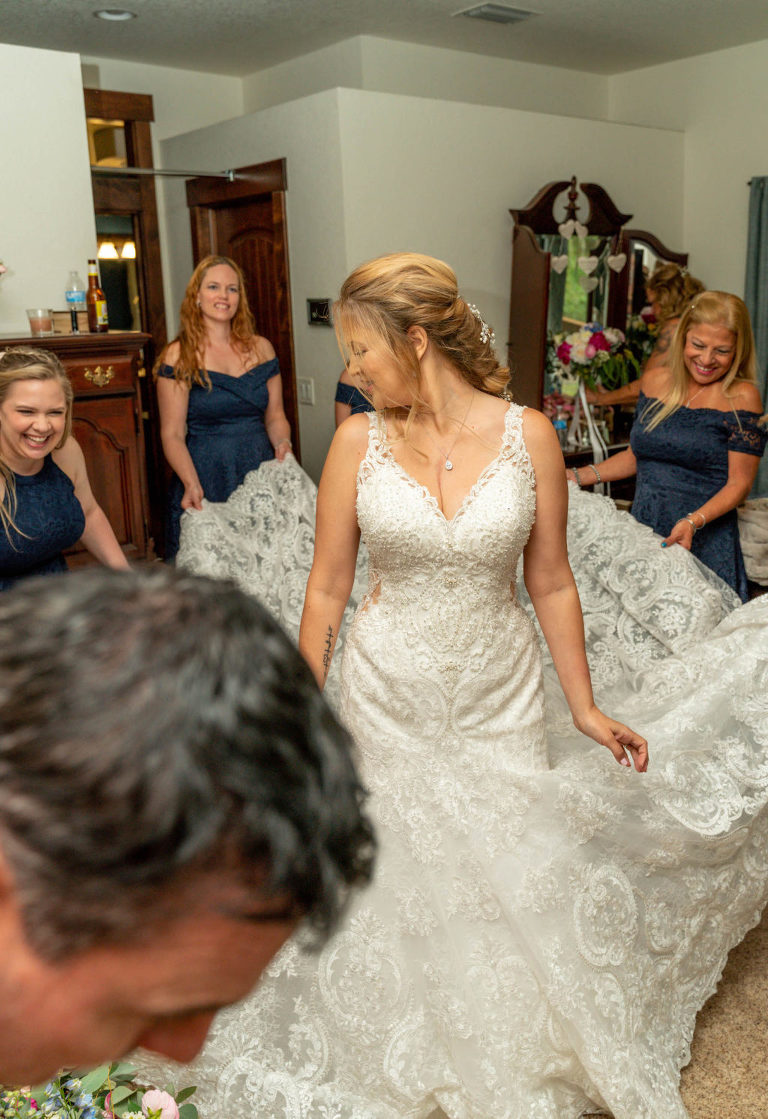 DIY Bride Wearing Lace V Neckline Wedding Dress and Bridesmaids in Navy Blue Dresses Holding Train