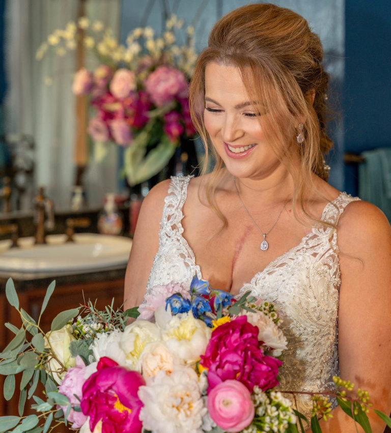 DIY Bride in Lace V Neckline Wedding Dress, Hair Pulled Back Holding Colorful Pink, White, Purple Floral Bouquet