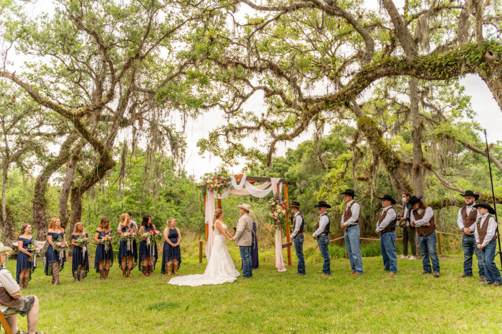 Tampa Intimate DIY Backyard Wedding Ceremony, Groom in Jeans and Tan Suit Jacket, Cowboy Hat, Bride in Lace Wedding Dress Exchanging Vows, Wooden Arch with Blush Pink and White Linen Draping, Colorful Pink, White and Blue with Greenery Floral Arrangements, Groomsmen in Brown Vests and Black Cowboy Hats