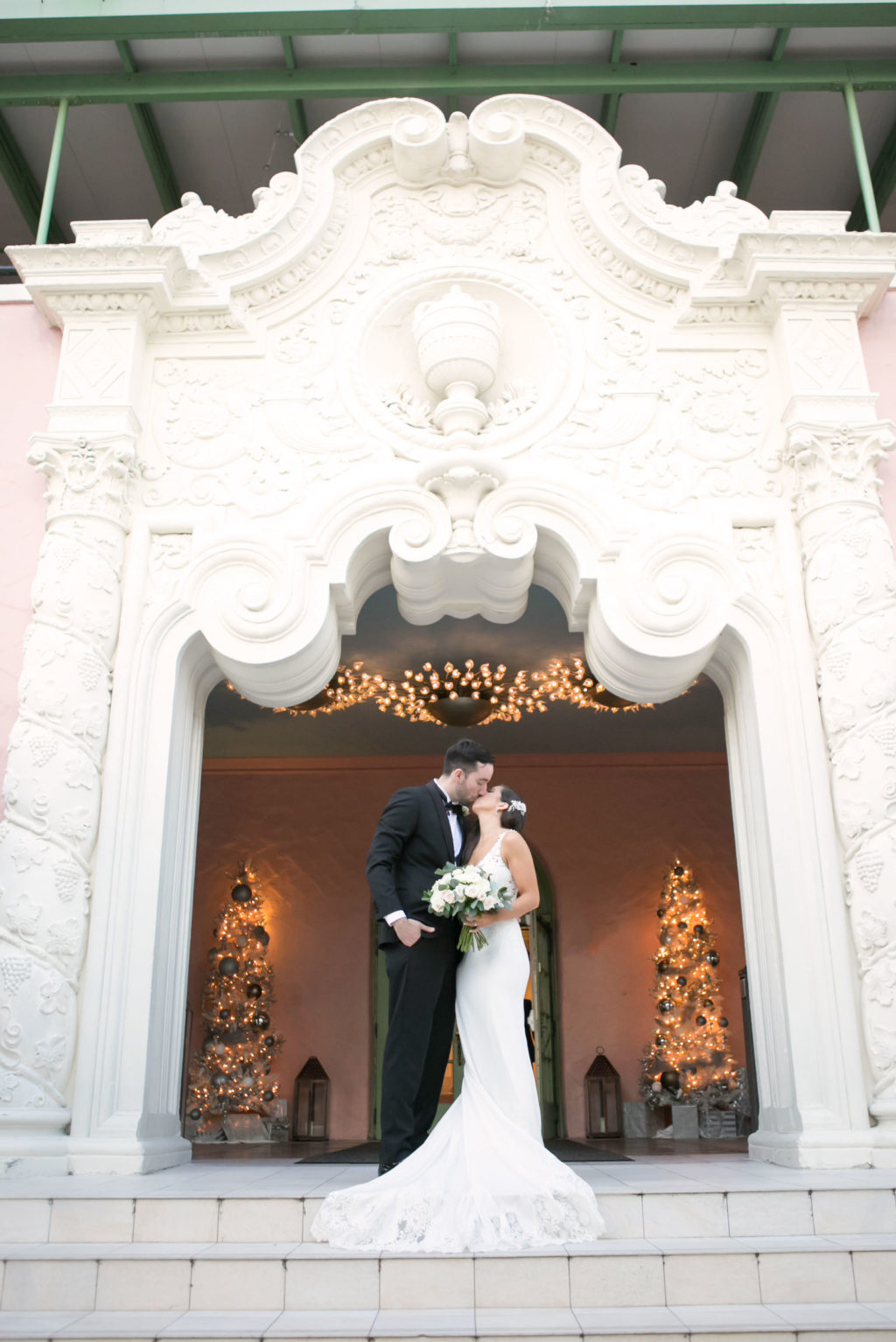 Elegant Classic Bride in Romantic Lace Train and Crepe Fitted Wedding Dress Holding White and Greenery Floral Bouquet, Groom in Classic Black Tux Under Arch of St. Pete Wedding Venue The Vinoy Renaissance | Tampa Bay Wedding Photographer Carrie Wildes Photography | Wedding Dress Shop Isabel O'Neil Bridal Collection