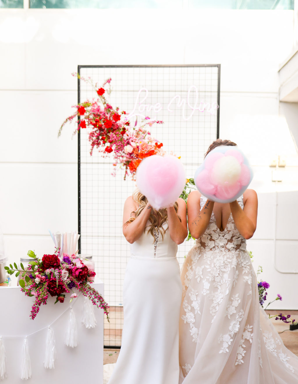 Modern Gay LGBTQ+ Pride Wedding, Lesbian Brides Holding Pink Cotton Candy, Rectangle Black Mesh Grid Arch with Colorful Rainbow Flower Arrangements   Tampa Bay Wedding Planner Stephany Perry Events   Rooftop Wedding Venue Hotel Alba