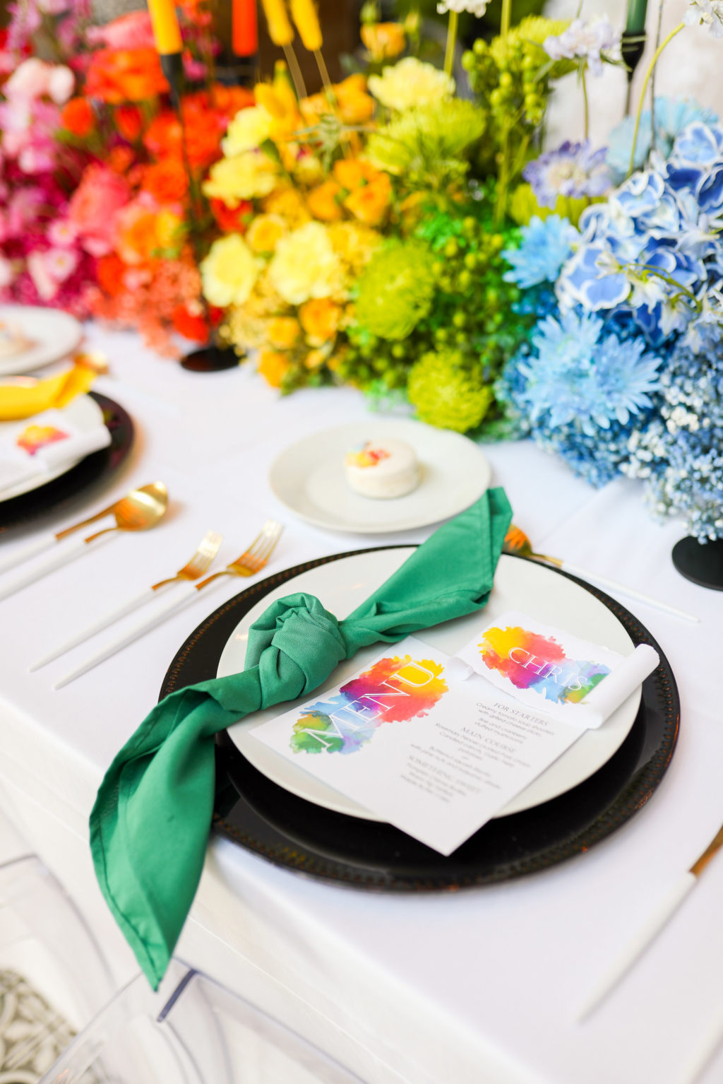 Modern Gay LGBTQ+ Pride Colorful Modern Rainbow Wedding Reception Decor, Green Napkin Linen, Rainbow Watercolor Menu Stationery, Black Charger, Blue, Green, Yellow, Orange and Red Flower Long Centerpiece and Candlesticks   Tampa Bay Wedding Planner Stephany Perry Events