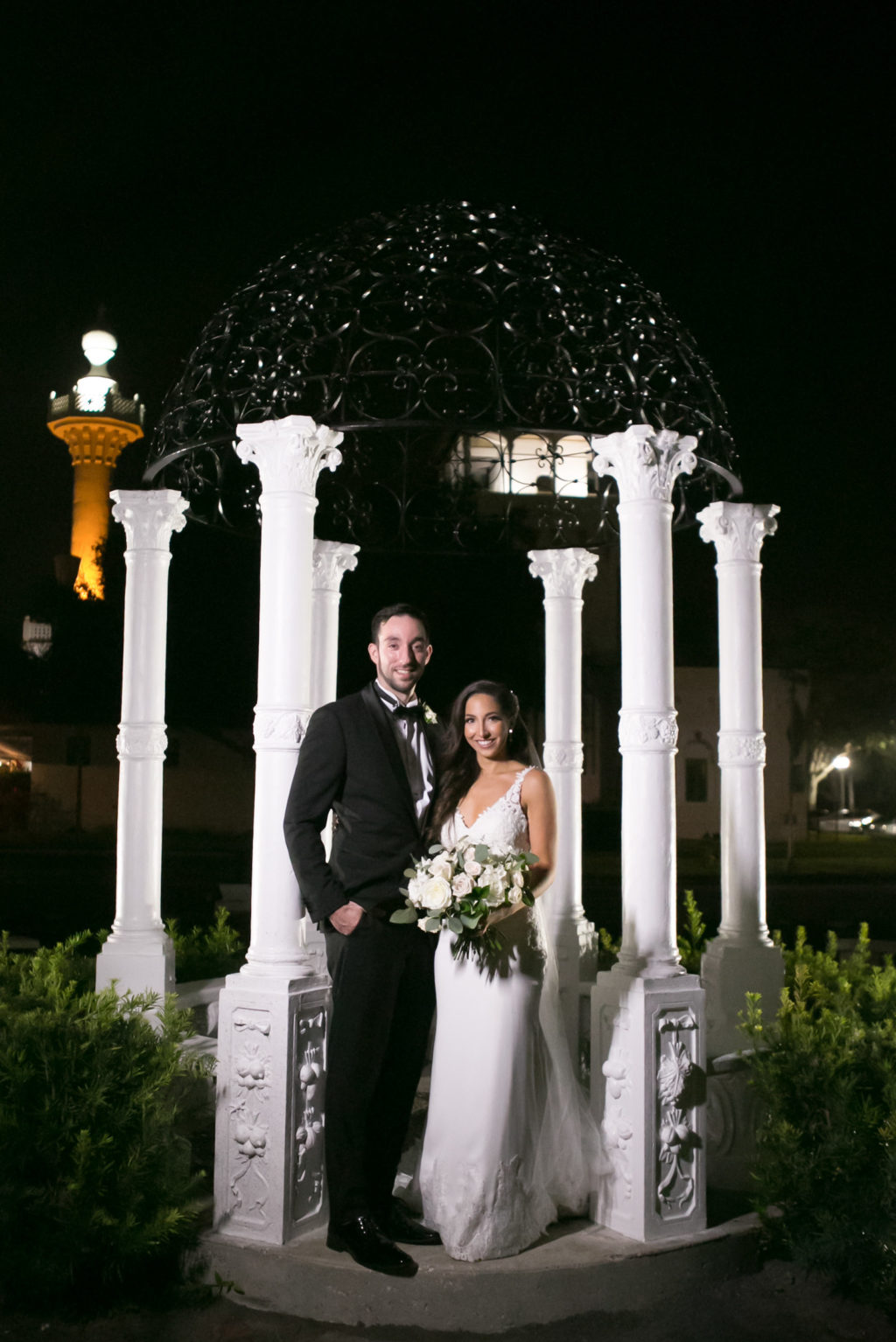 Elegant Bride and Groom Nighttime Photo Under White Pedestals | Tampa Bay Wedding Photographer Carrie Wildes Photography | Wedding Dress Shop Isabel O'Neil Bridal Collection