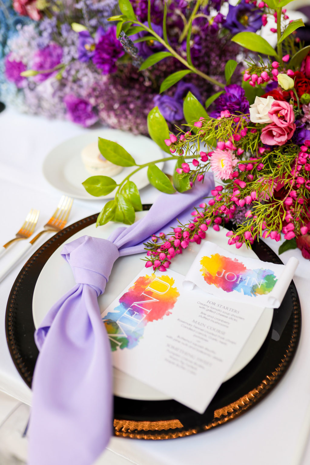 Modern Colorful Rainbow Gay LGBTQ+ Pride Wedding Reception Decor, Purple Linen Napkin, Black and Gold Charger, Watercolor Rainbow Stationery Menu, Pink and Purple Flower Centerpiece   Tampa Bay Wedding Planner Stephany Perry Events