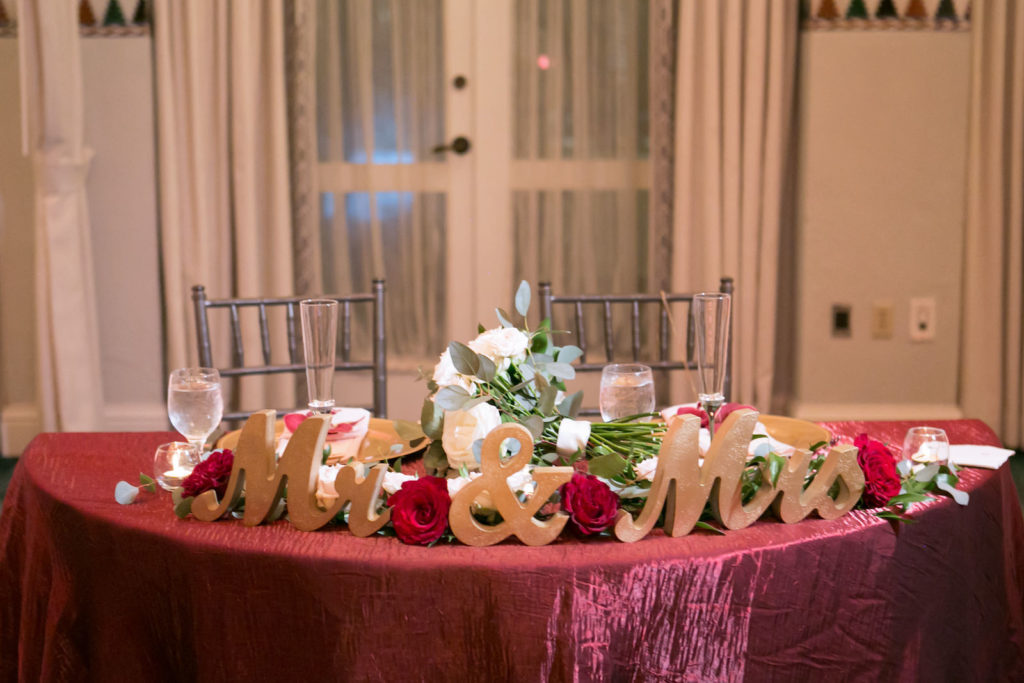 Elegant Wedding Reception Decor, Sweetheart Table with Burgundy Red Table Linen, Gold Mr and Mrs Sign Letters, Greenery and Burgundy Roses | Tampa Bay Wedding Photographer Carrie Wildes Photography