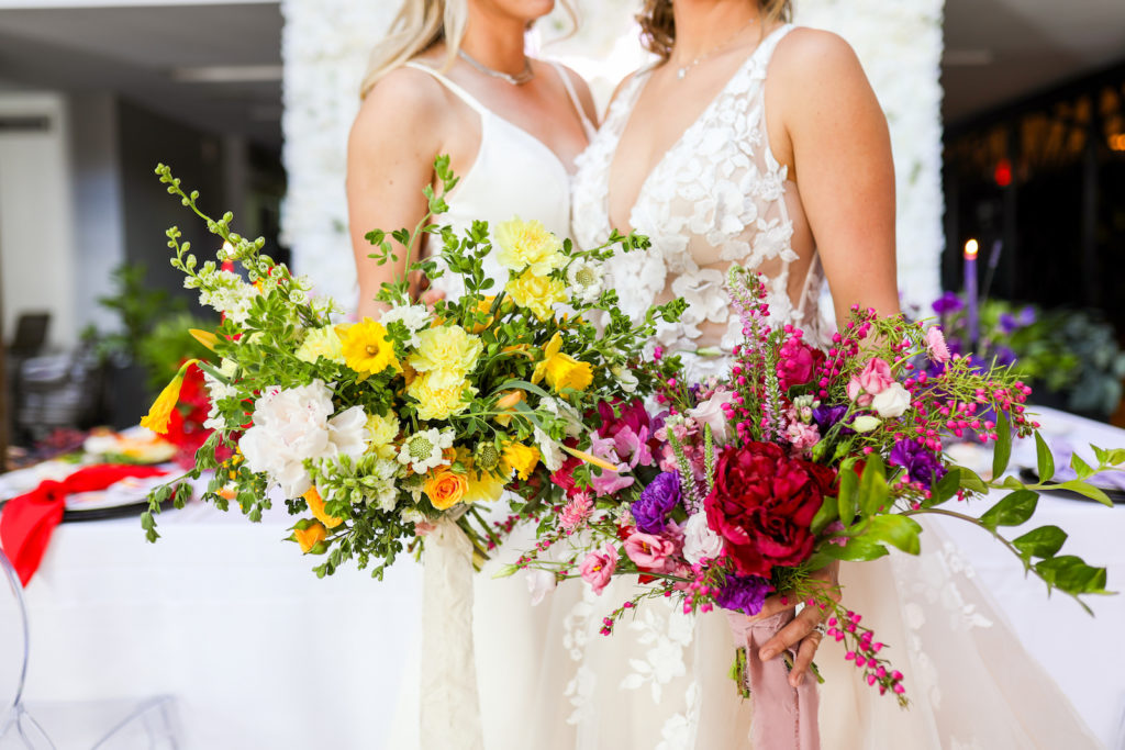 Colorful Modern Rainbow Gay LGBTQ+ Pride Wedding Reception Decor, Lesbian Brides Holding Yellow, Pink and Purple Wild Floral Bouquets, White Flower Wall Backdrop   Tampa Bay Wedding Planner Stephany Perry Events   Wedding Venue Hotel Alba