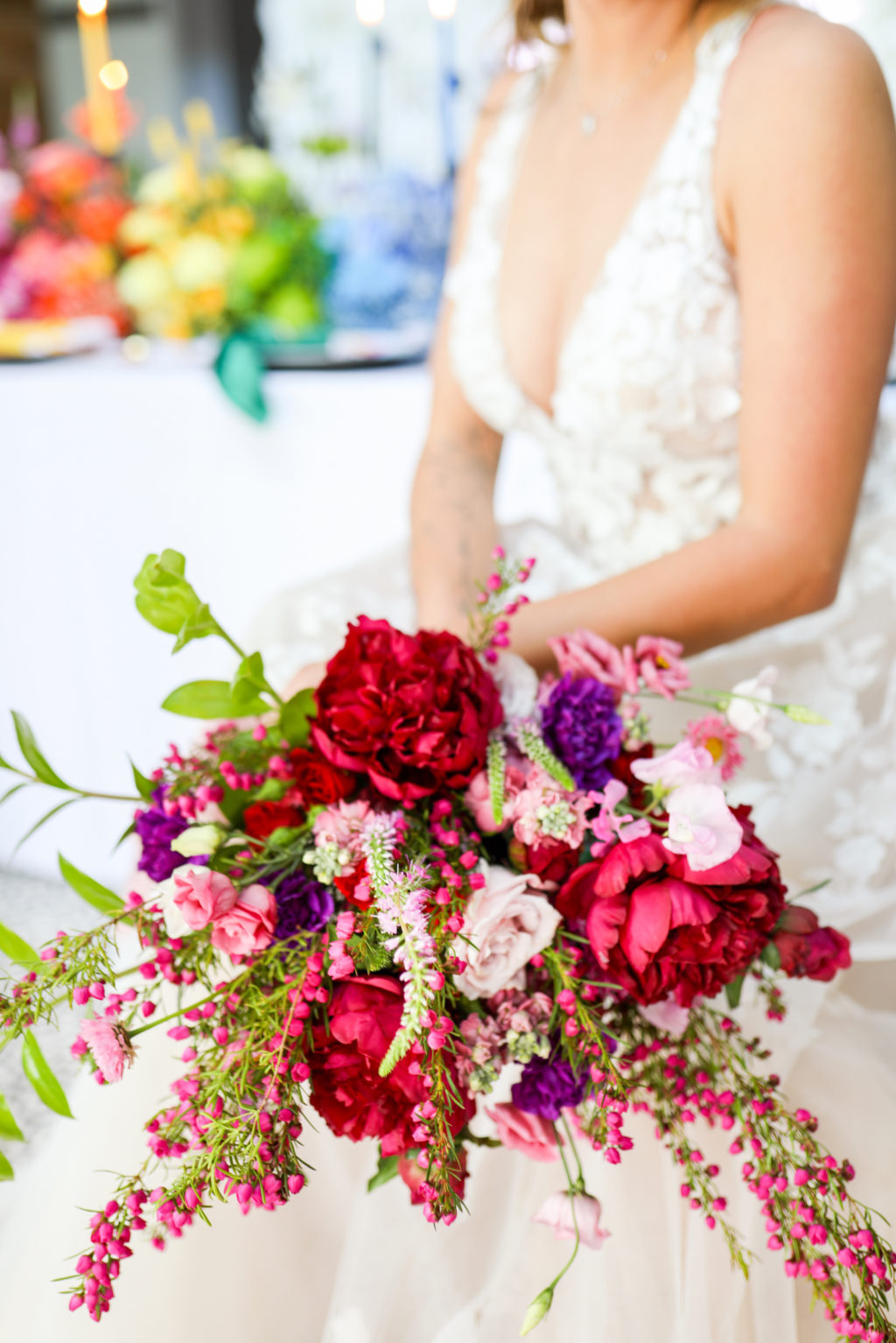 Colorful Modern Rainbow Gay LGBTQ+ Pride Wedding Reception Decor, Lesbian Bride Holding Wild Red, Purple and Pink Floral Bouquet   Tampa Bay Wedding Planner Stephany Perry Events