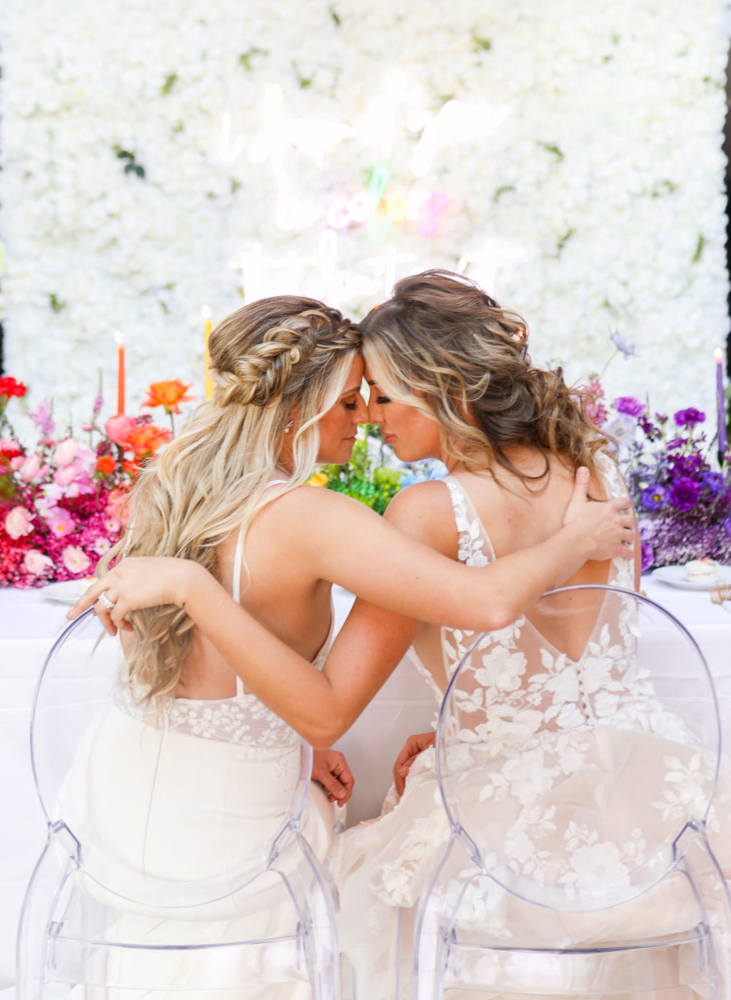 Colorful Rainbow Modern Gay LGBTQ+ Wedding Reception Decor, Lesbian Brides Sitting in Acrylic Ghost Chairs, White Flower Backdrop with Neon Sign, Pink, Red, Orange, Green, Yellow, Purple Flower Centerpiece   Tampa Bay Wedding Planner Stephany Perry Events