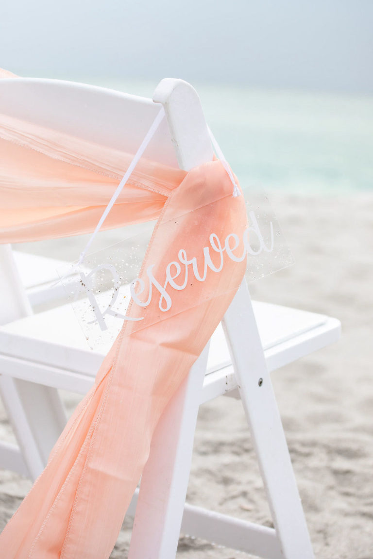 Sarasota Florida Beach Wedding White Folding Ceremony Chair with Acrylic Clear Reserved Sign and Peach Sash