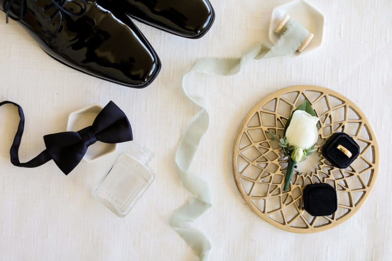 Groom Wedding Accessories, Black Bowtie, Glossy Black Tuxedo Dress Shoes, Bottle of Cologne, Yellow Gold Wedding Ring in Black Velvet Ring Box On Gold Geometric Tray | Tampa Bay Wedding Photographer Lifelong Photography Studio