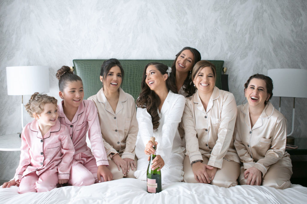Florida Bride, Bridesmaids in Champagne Silk Pajamas, Flower Girls in Pink Silk Pajamas Getting Wedding Ready on Bed with Champagne | Tampa Bay Wedding Photographer Carrie Wildes Photography