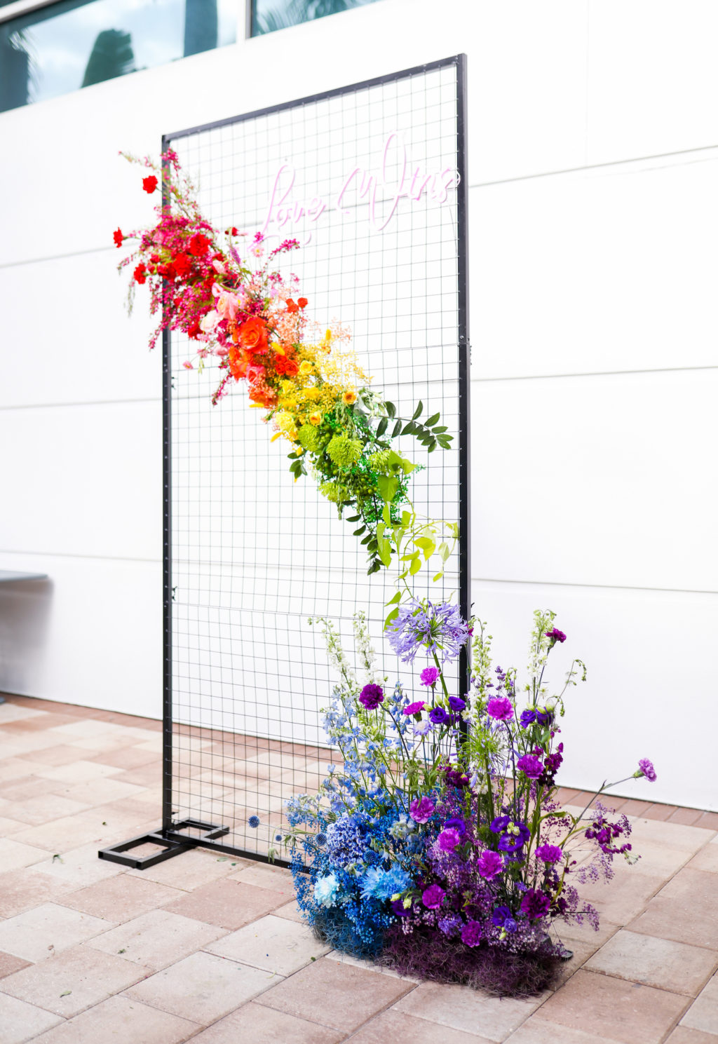 Modern Gay LGBTQ+ Pride Wedding Ceremony Decor, Rectangle Black Metal Grid Mesh Arch with Colorful Rainbow Pink, Red, Yellow, Green, Blue and Purple Flowers and Neon Pink Sign   Tampa Bay Wedding Planner Stephany Perry Events