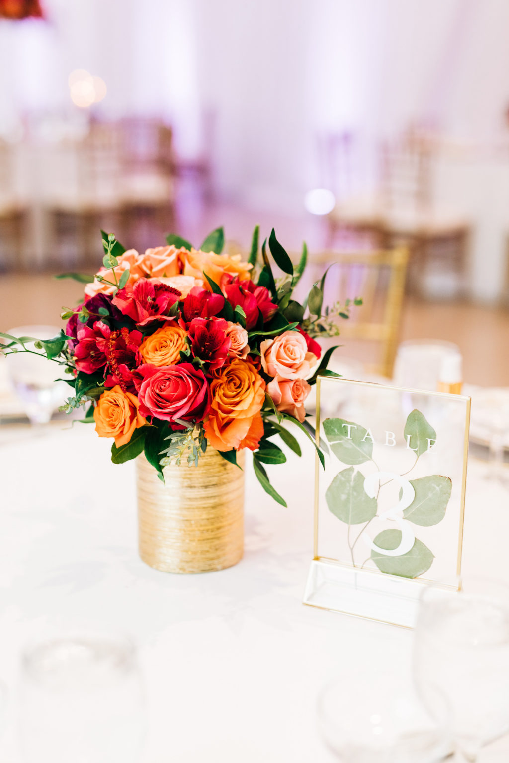 Elegant Wedding Reception Decor, Vibrant and Small Colorful Red and Orange Roses Floral Centerpiece in Gold Vase   Tampa Bay Wedding Florist Monarch Events and Design   Wedding Rentals Kate Ryan Event Rentals
