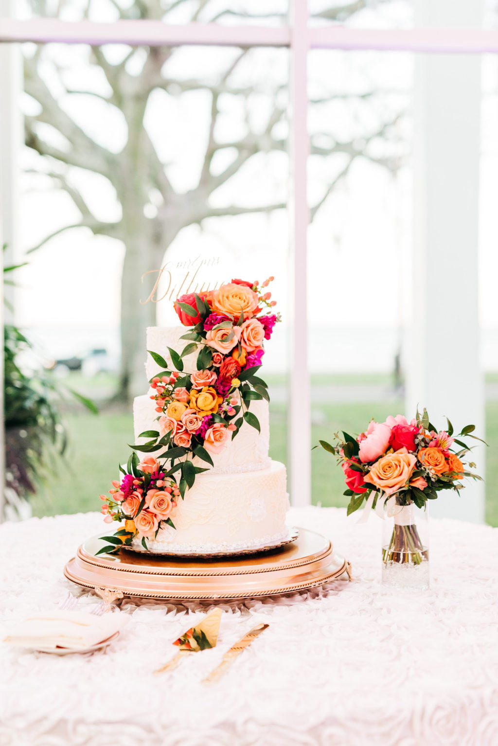 Elegant Three Tier White Wedding Cake with Vibrant Cascading Pink, Orange and Greenery Flowers   Tampa Bay Florist Monarch Events and Design