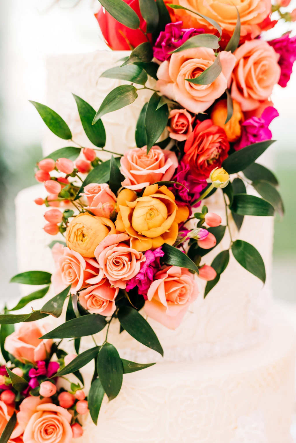 Elegant Three Tier White Wedding Cake with Vibrant Cascading Pink, Orange Roses and Greenery Flowers   Tampa Bay Florist Monarch Events and Design