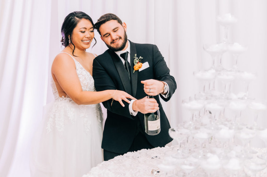 Elegant Bride and Groom Opening Bottle of Champagne for Champagne Tower