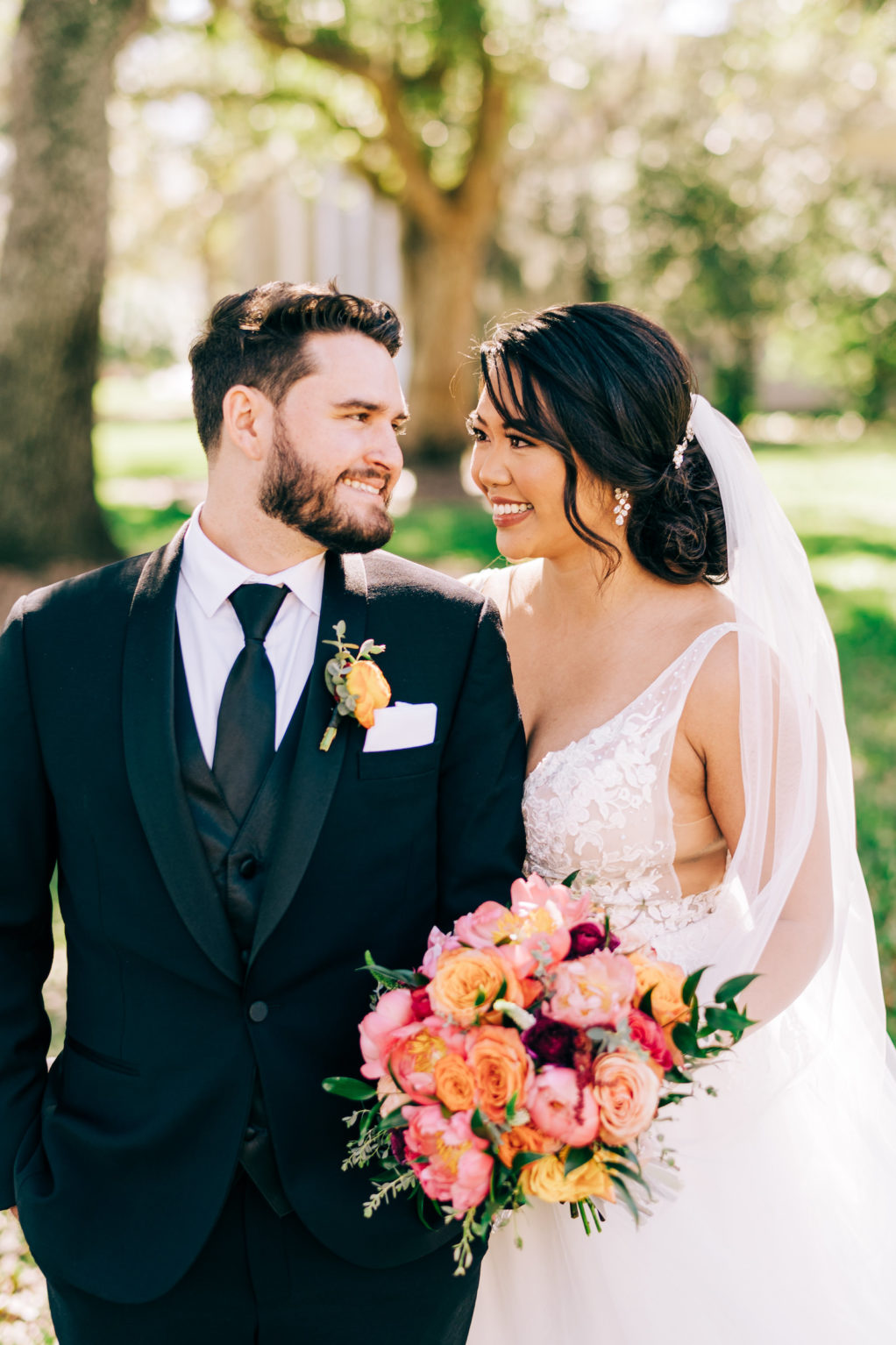 Classic Bride Wearing Plunging V Neckline Lace with Straps and Tulle A-Line Wedding Dress Holding Vibrant Colorful Pink, Orange Roses and Red Floral Bouquet, Groom in Black Tuxedo and Orange Rose Boutonniere   Tampa Bay Wedding Florist Monarch Events and Design