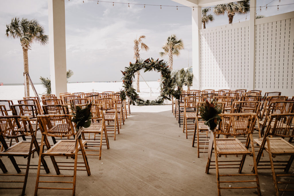 Tropical Elegant Waterfront Wedding Ceremony Decor, Bamboo Chairs, Circular Palm Fronds and Leaves Wedding Arch | Wedding Venue Hilton Clearwater Beach | Tampa Bay Wedding Florist Iza's Flowers