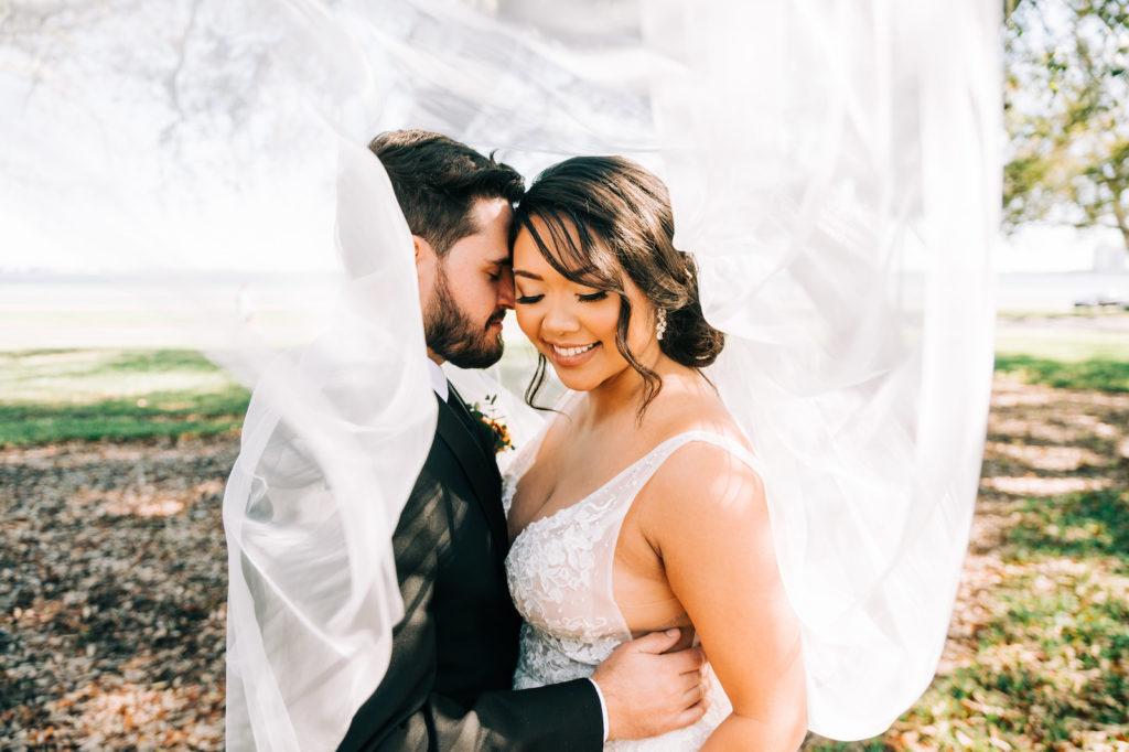 Romantic Bride and Groom Under Wedding Veil Photo