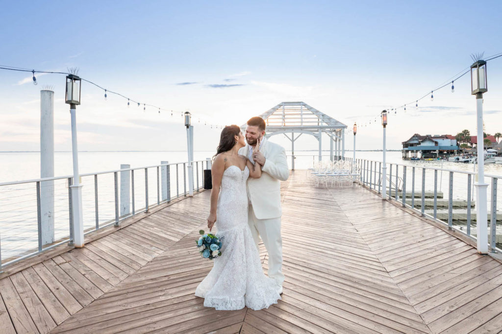 Waterfront Wedding Ceremony Portraits with Overwater Pier and White Pergola with Draping and Greenery | Tampa Wedding Venue The Godfrey
