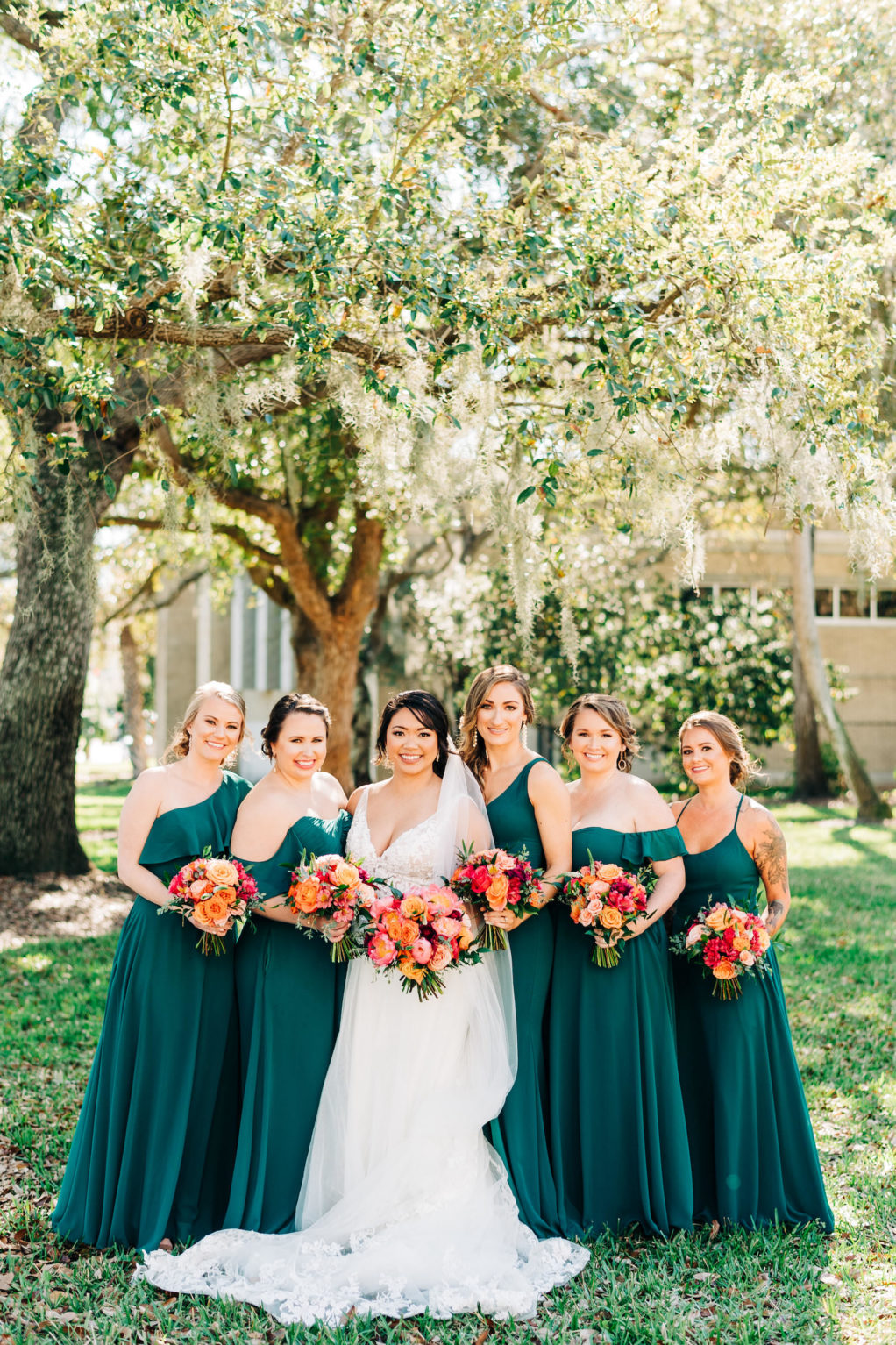 Classic Bride and Bridesmaids Outdoors in Mix and Match in Emerald Green Dresses Holding Vibrant Colorful Pink, Orange and Red Floral Bouquets   Wedding Venue Tampa Garden Club   Tampa Bay Wedding Florist Monarch Events and Design