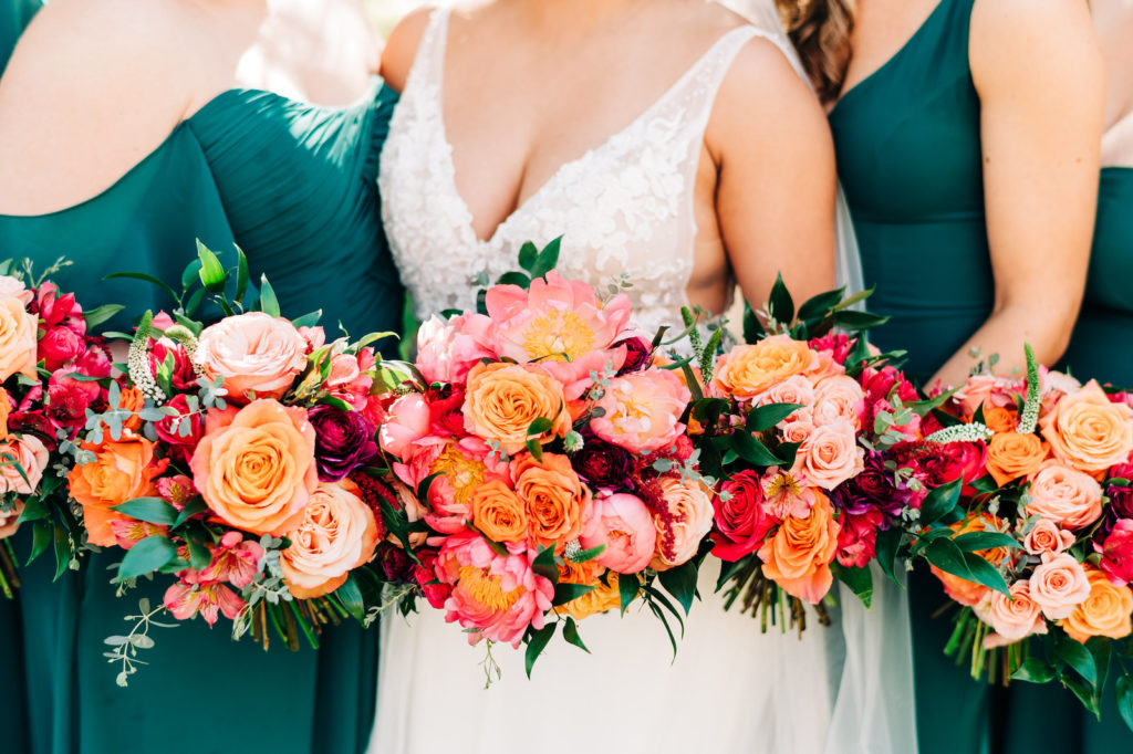 Classic Bride and Bridesmaids Outdoors in Mix and Match in Emerald Green Dresses Holding Vibrant Colorful Pink, Orange and Red Roses with Greenery Floral Bouquets   Wedding Venue Tampa Garden Club   Tampa Bay Wedding Florist Monarch Events and Design