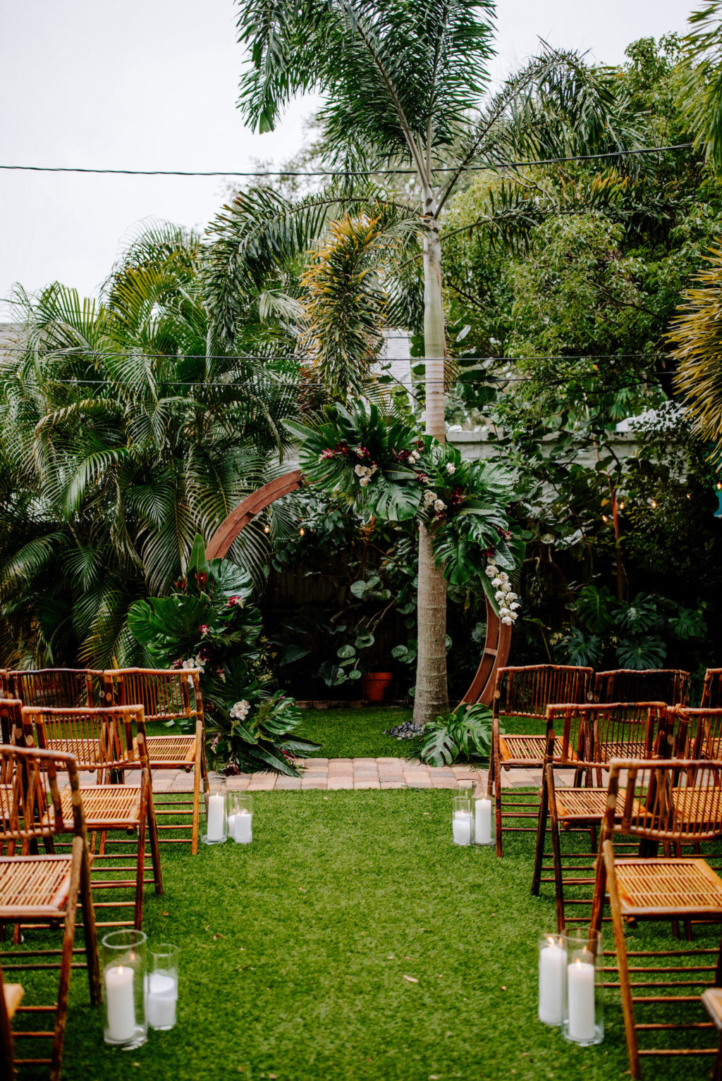 Outdoor Florida Wedding, Backyard Ceremony with Jungle Inspired Decor with Bamboo Circle Arch and Folding Chair Rentals, Bright Greenery with pops of Pink Florals and White Orchids | St. Petersburg Wedding Planner Parties A'La Carte