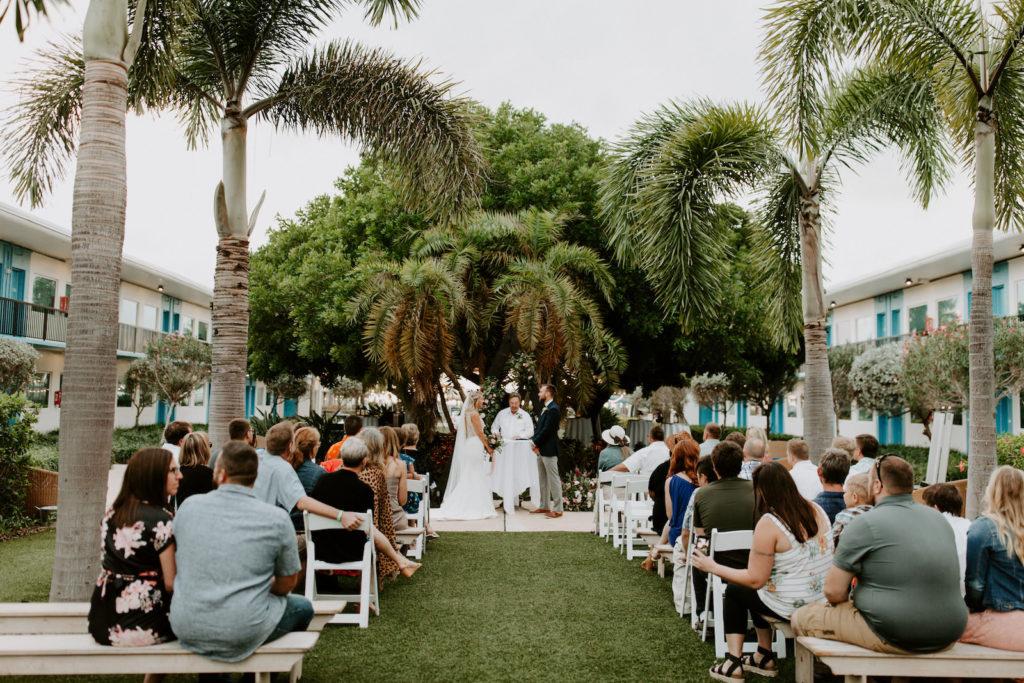 Tropical Garden Bride and Groom Exchanging Wedding Vows During Outdoor Wedding Ceremony | St. Pete Wedding Venue Postcard Inn