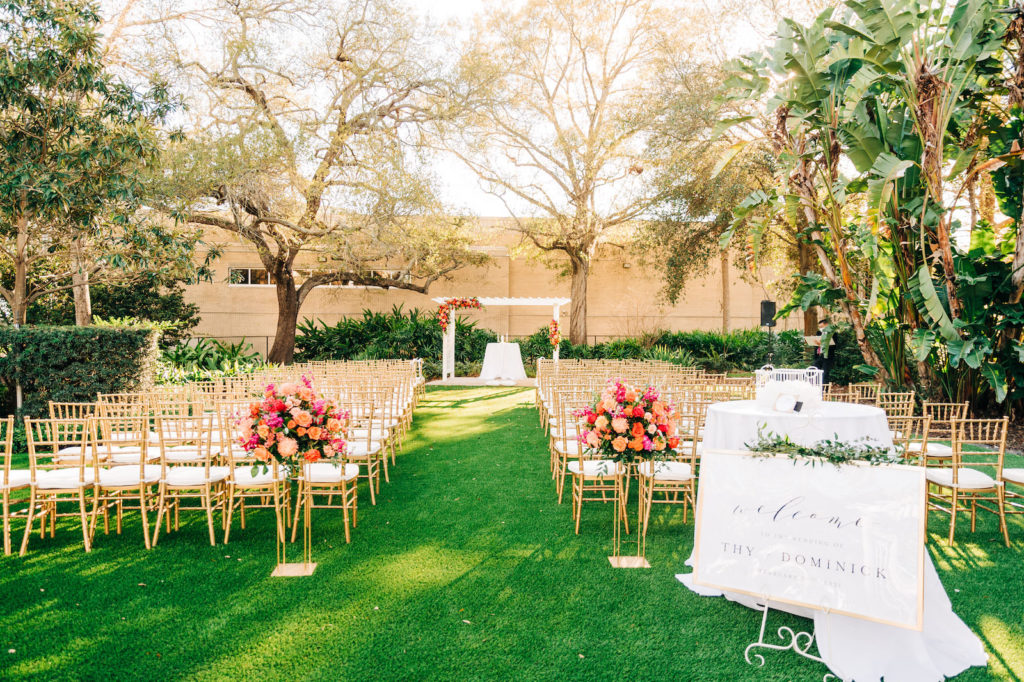 Outdoor Garden Wedding Ceremony Decor, Gold Chiavari Chairs, White Pergola, Vibrant and Colorful Pink, Orange and Red Floral Arrangements on Gold Geometric Stands, White Welcome Sign in Gold Frame with Greenery Garland | Wedding Venue Tampa Garden Club | Wedding Florist Monarch Events and Design | Wedding Rentals Kate Ryan Event Rentals